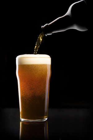 beer pint: Beer being poured from a beer bottle into a pint glass with a reflection at the base, against black background Stock Photo