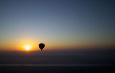 A hot air balloon silhouetted against the rising sun at dawn over the river Nile in Egypt. photo