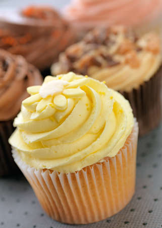 buttercream: Cupcakes with a lemon cupcake at the front, shallow focus, focus on lemon buttercream.