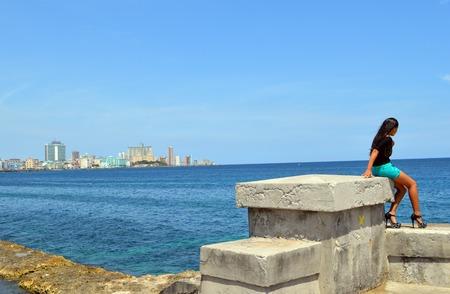 cuba girl: Havana Cuba: Cuban girl on the Malecon against Havana skyline Stock Photo