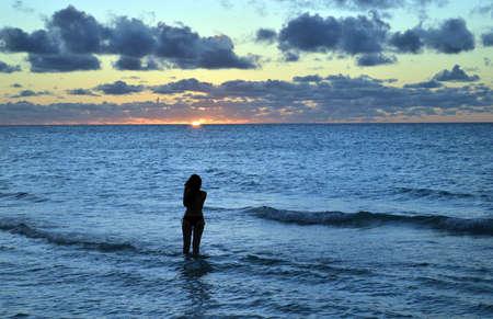 varadero: Pretty girl photographs Caribbean sunset at Varadero beach, Cuba Stock Photo