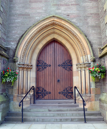 wrought: Wooden door, with hanging flower baskets to either side, on St Matthews Church, Tay Street, Perth, Scotland