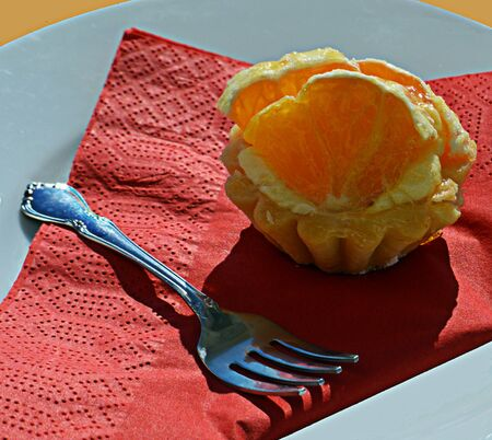 serviette: A cupcake topped with orange slices on a red serviette sitting plate with silver cake fork Stock Photo
