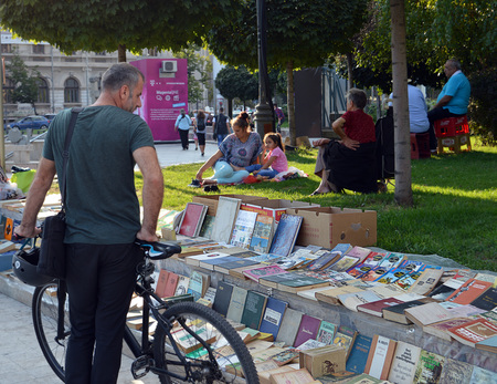 sidewalk sale: A cyclist stops to look at books being sold on the pavement at Piata Universitatii University Square Bucharest, Romania Editorial