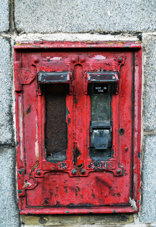 royal mail: A long-disused postage stamp dispenser on a granite wall in Aberdeen, Scotland