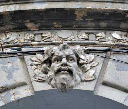 hombre con barba: Bearded man, possibly Neptune, as figure on keystone of entrance arch on former PTTR hospital, Bucharest , Romania