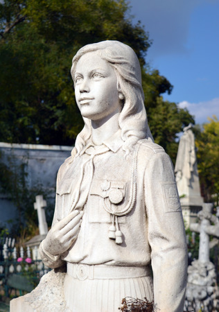 pioneers: Memorial statue of young girl in the uniform of the Pioneers on a tomb in the Orthodox section of the Cimitriul Bellu Serban Voda Cemetery, Bucharest, Romania. Editorial
