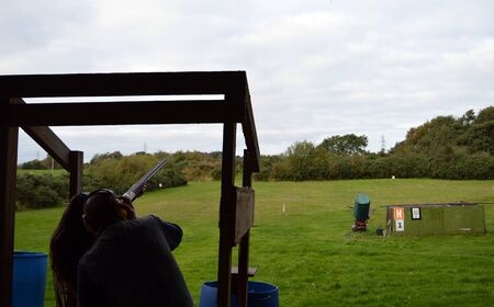 instruct: An instructor supervises a female clay pigeon shooter on a range in Fife Scotland