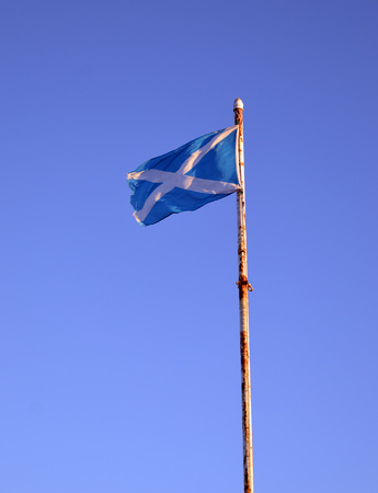 flagpole: The Scottish saltire flag flies on a rusty flagpole at Torry Battery, Aberdeen, Scotland