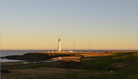 bathed: Girdleness lighthouse, Aberdeen, Scotland is bathed in evening sunshine.