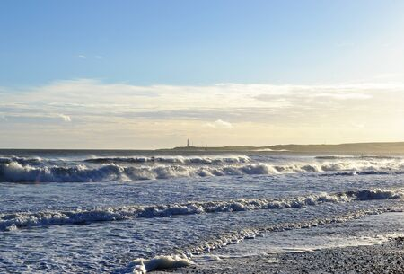 groynes: Waves crash in on Aberdeen beach in bright winter sunshine, Girdleness and Souh pier lighthouses in the distance