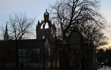 crown spire: Late afternoon winter light forms silhouettes of trees and the 15th century Kings College Chapel in Old Aberdeen.