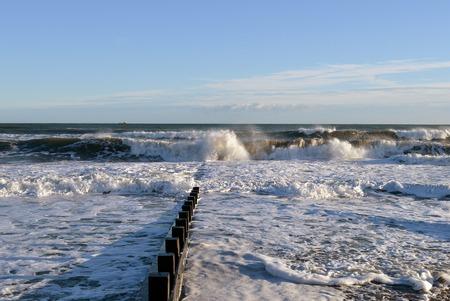 December waves crash on a groyne at Aberdeen beach, Scotland