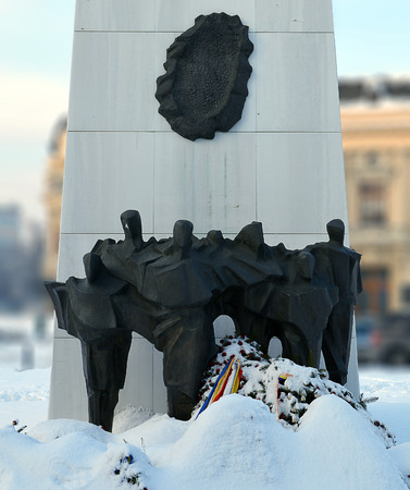 Bronze figures stand in snow at the base of the Rebirth Monument in Revolution Square, Bucharest, Romania