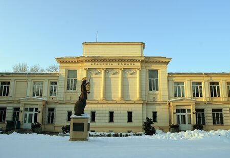 athena: BUCHAREST, ROMANIA - 26 JANUARY 2016: Late afternoon winter sun imbues the headquarters of the Romanian Academy on Calea Victoriei and the statue of Athena in front with a golden glow.