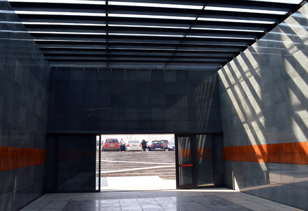 holocaust: BUCHAREST, ROMANIA - 5 FEBRUARY 2016: The Holocaust Memorial evokes a cell with ceiling dividers and their shadows echoing prison bars. Copper panels bear first names of some of the victims. Editorial