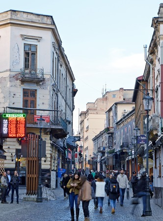 fill up: BUCHAREST, ROMANIA - 4 FEBRUARY 2016: The cobbled streets of the Old Town start to fill up at the end of the day. Foreign exchange rates for tourists are prominently displayed.