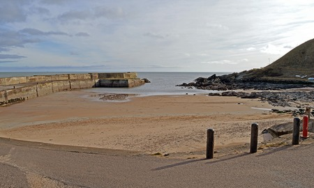 er: Beach, pier and harbour at the for,er fishing village of Collieston on the Aberdeenshire coast in the North East of Scotland.