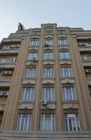 suggests: BUCHAREST, ROMANIA - 21 FEBRUARY 2016: The art deco facade of an apartnment block looks impressive 80 years on but the High Seismic Risk circle on the building suggests its days are numbered.