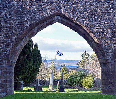 scottish flag: Una bandiera scozzese vola accanto alle vecchie tombe intorno alla rovina della chiesa am XI secolo nel Perthshire, in Scozia