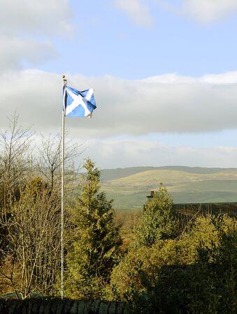 scottish flag: bandiera scozzese vola nella luce della sera in Muthill con le colline Perthshire in background. Archivio Fotografico