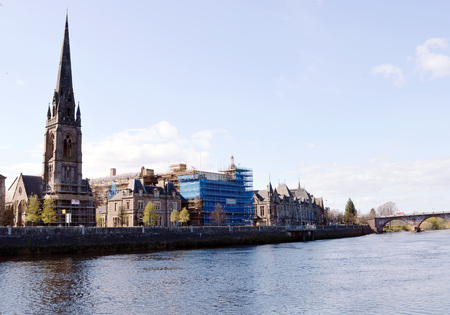 necessity: PERTH, SCOTLAND - 19 APRIL 2016:  St Matthews Church and Necessity Brae, former HQ of General Acciident Assurance, undergo renovation on Tay Street with the County Buildings and Perth Bridge behind.