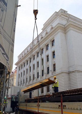 programme: Men supervising a crane lifting girders during a building renovation programme in Bucharest, Romania.