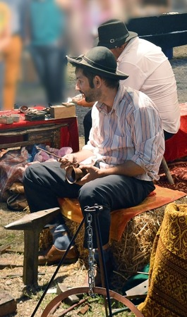 gitana: Bucarest, Rumania - 9 DE SEPTIEMBRE DE 2016: Gypsy artesanos muestran sus habilidades para trabajar los metales en una Feria de Artesanía de los Balcanes, Editorial