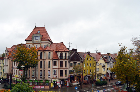 masuria: GOLDAP - POLAND: 7 OCTOBER 2016: The south side of the market square Plac Zwyciestwa) stands nearly deserted on a wet and cold auttumn day.