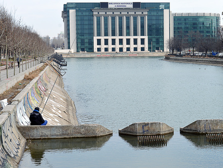 BUCHAREST, ROMANIA - 21 FEBRUARY 2017: A man fishes optimistically in the River Dambovita on the edge of Piata Unirii (Unity Square) in the centre of Bucharest, Romania with the National Library in the background.