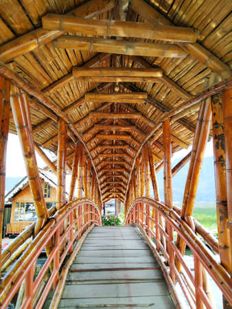 Bamboo bridge over a river in the city of La Cocha in the Colombian Mountains. This photo shows a perspective from inside a bamboo bridge located in the port of La Cocha lagoon - El Encano, Narino C