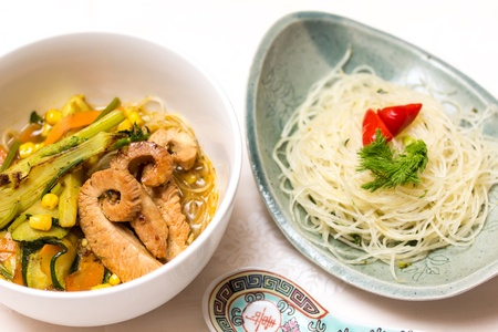 Asian chicken vegetable soup with spices and rice noodles photo