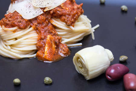 bolognaise: Spaghetti bolognaise in a black plate with capers, olives and artichoke