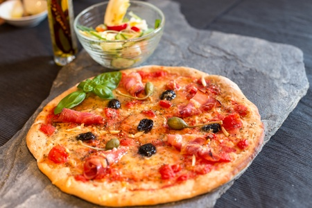 stone bowl: Home-made pizza with salad on stone slate