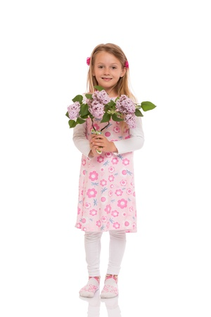 Smiling little girl with long hair wearing summer dress standing and holding lilac flowers. Isolated on white background. photo