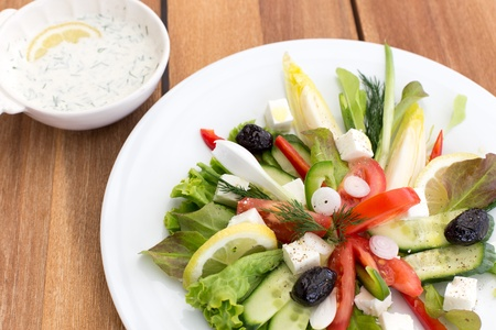 Greek salad with feta, tomatoes, cucumber, peppers and black olives. With bowl of sauce on a wooden table. photo