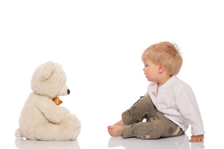 Little boy with blond hair sitting on the floor and looking at her teddy bear. Isolated on white background. photo