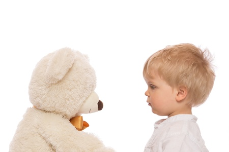 Cute child with blond hair looking her teddy bear. Isolated on white background. photo