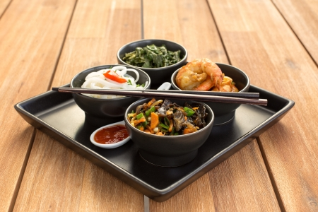 Traditional chinese dish on a square plate in black bowls with shrimp, rice noodles, kale (green cabbage) and fried vegetables. Composed with ceramic spoon with spicy red sauce and chinese chopsticks. Composition on a old styled wooden table. photo