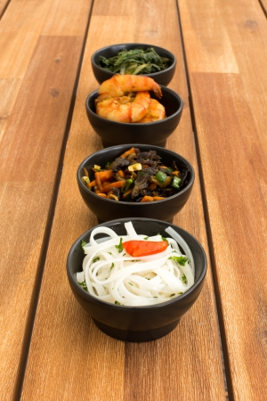 Asian food composed with four black bowls with shrimps, rice noodles, kale (green cabbage) and fried vegetables. Composition on a old styled wooden table. photo
