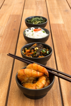 Japanese food composed with four black bowls with shrimps, rice noodles, kale (green cabbage), fried vegetables and asian chopsticks. Composition on a old styled wooden table. photo