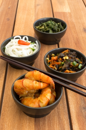 Asian vegetarian food composed with four black bowls with shrimps, rice noodles, kale (green cabbage), fried vegetables and chinese chopsticks. Composition on a old styled wooden table. photo