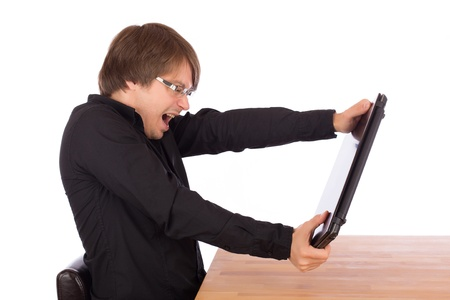 choleric: Angry young business man wants to destroy his laptop on the table. Isolated on white background.