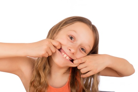 derision: Happy girl make a grimace. Isolated on a white background.