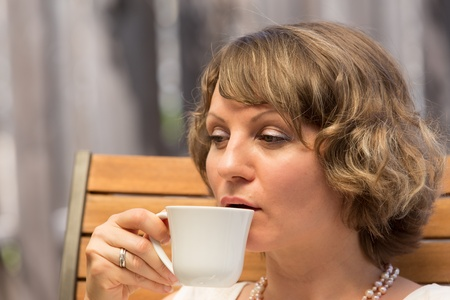 Attractive woman drinking a cup of coffee on wooden chair. photo