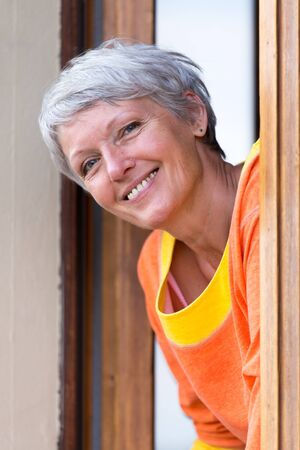 Smiling modern mature woman with grey hairs looking from the window. photo