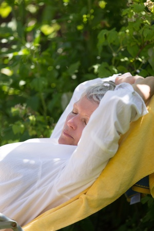 Senior woman with grey hairs sleeping on lounger in her garden. photo
