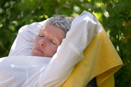 Senior woman with white hairs sleeping on lounger in her garden. photo