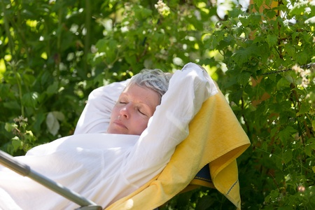 Mature woman with white hairs sleeping on lounger in her garden. photo