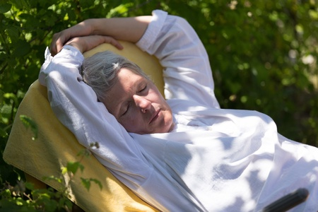 Mature woman with grey hairs sleeping on lounger in her garden. photo